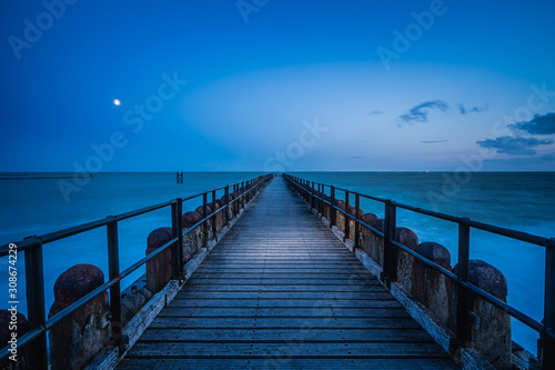 Cuadros en Lienzo Long wooden pier extends over water toward the horizon