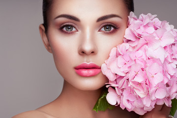 Portrait of beautiful young woman with flowers. Brunette woman with luxury ma...