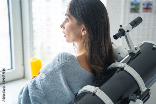 Thoughtful astronomer with her telescope stock photo Wallpaper Mural