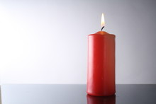 Isolated Red Candle, White Background, Burning Candle On A Table