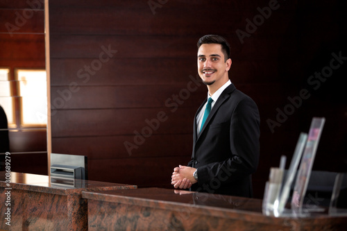 Fotografía Young receptionist standing behind the front desk