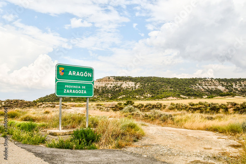 Fotomural sign on road in mountains, photo as a background