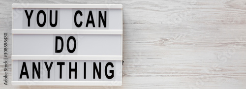 Photo 'You can do anything' words on a lightbox on a white wooden background, top view