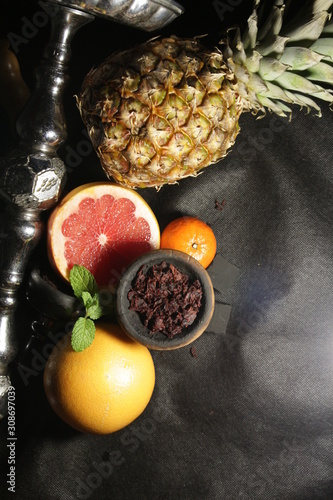 bowl with tobacco for hookah. fruits on a dark background. smoking nargole
