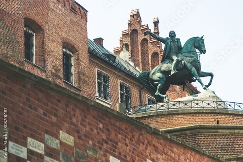 Fotografie, Tablou Names in the  brick wall on the way up to Wawel Royal Castle, a bronze statue of