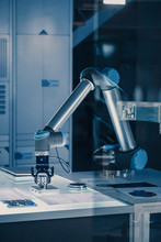 Vertical Shot Of Futuristic Artificial Intelligence Robotic Arm Operates And Moves A Metal Object, Picks It Up And Puts It Down. Scene Is Taken In A High Tech Research Laboratory With Modern Equipment