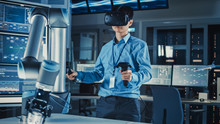 Professional Japanese Development Engineer In Blue Shirt Is Controlling A Futuristic Robotic Arm With A Virtual Reality Headset And Joysticks In A High Tech Research Laboratory With Modern Equipment.
