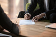 Close up businessmen signing partnership agreement, making legal deal