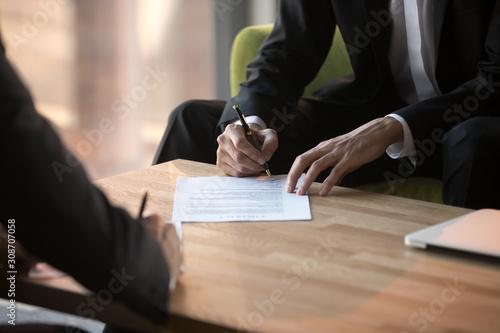 Stampa su Tela  Close up businessmen signing partnership agreement, making legal deal