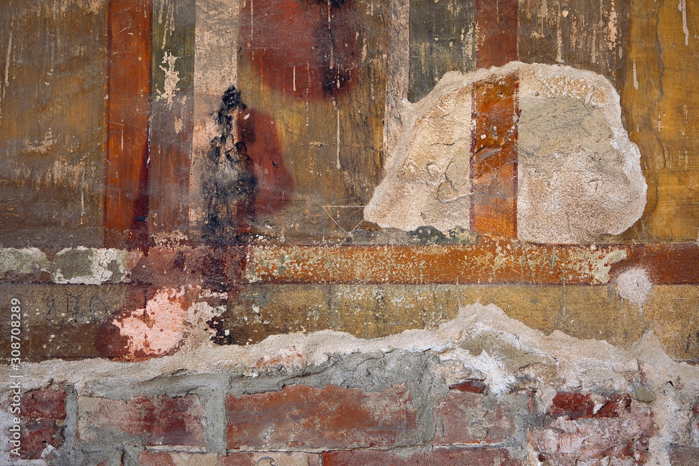 Grungy colorful vintage painted wall with lines and stripes. Very old paint  background with plaster stains. Rustic retro style damaged surface. Shades of yellow, green and ocher. Dirty wall texture.
