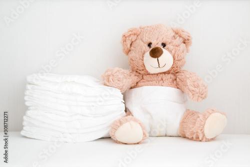 Fotografiet Brown teddy bear sitting in baby bed
