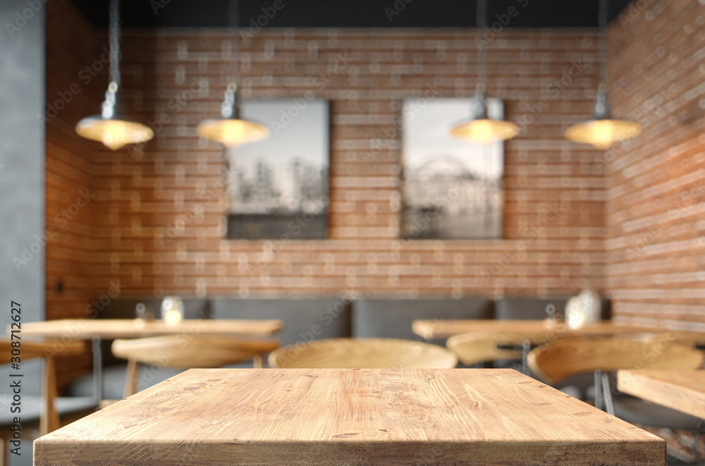 Fototapeta Empty coffee table over defocused coffee shop background with copy space