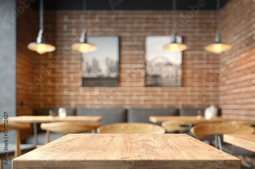 Obraz na plátně Empty coffee table over defocused coffee shop background with copy space