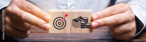 Foto Businessman collects wooden blocks with the image of the goal and money