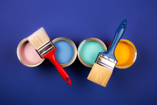 Four Open Cans Of Paint With Brushes On Blue Background. Yellow, Blue, Pink, Turquoise Colors Of Paint. Top View.