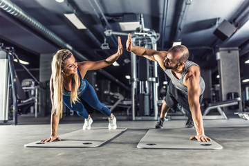 Fototapeta na wymiar Sport couple doing plank exercise workout in fitness centrum. Man and woman practicing plank in the gym