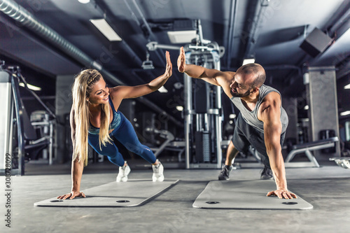 Fototapeta Sport couple doing plank exercise workout in fitness centrum. Man and woman practicing plank in the gym obraz