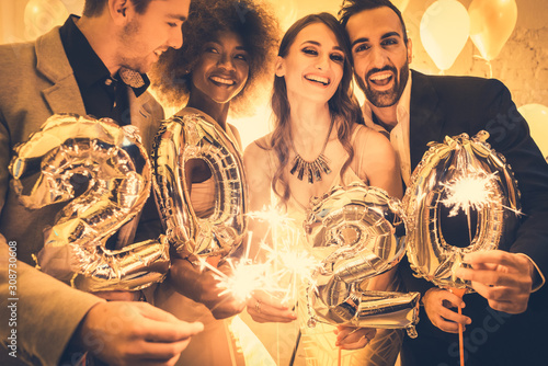 Men and women celebrating the new year 2020 - 308730608