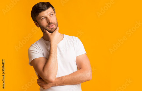 Pensive middle-aged guy standing touching chin thinking over yellow background Canvas Print