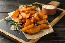 Slices Of Baked Potato Wedges, Rosemary, White Sauce, Kitchen Board On Wooden Background, Space For Text. Closeup