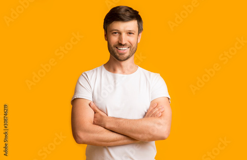 Mature Guy Crossing Hands Smiling At Camera Standing In Studio Tablou Canvas