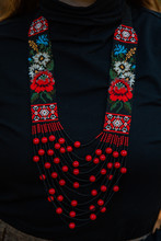 A Beautiful Gerdan Decoration In Red Shades On The Neck With A Black Sweater. Coral Color Beads With Rose Patterns. Handwork From Beads.