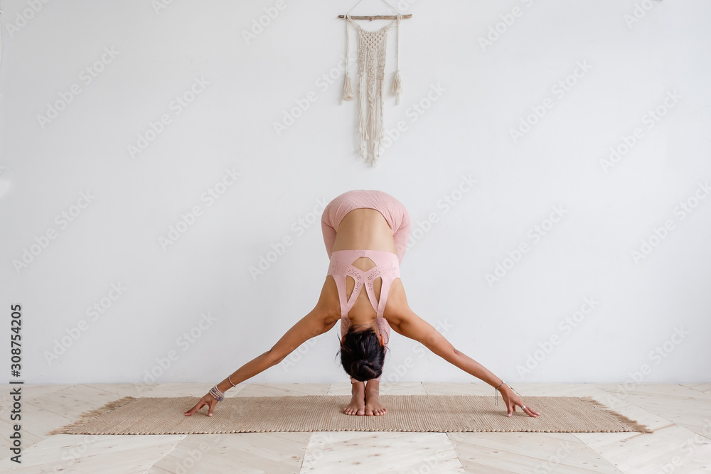 Fototapeta Cute slim young unidentified brunette woman doing yoga uttanasana while standing on rug on the floor in a pink barefoot suit. Young woman is training at home. Places for advertising