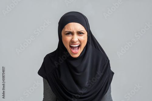 Tablou Canvas Angry muslim girl in hijab screaming loud, emotionally protesting about somethin