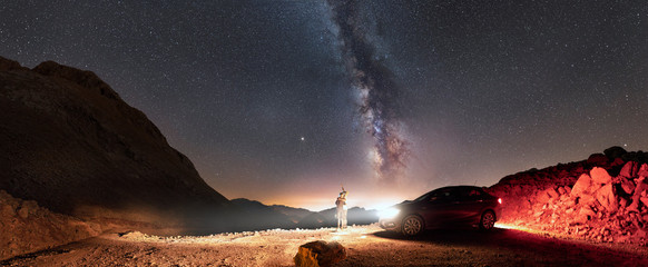 Panorama of milky way and two people standing near car and looking up to the sky