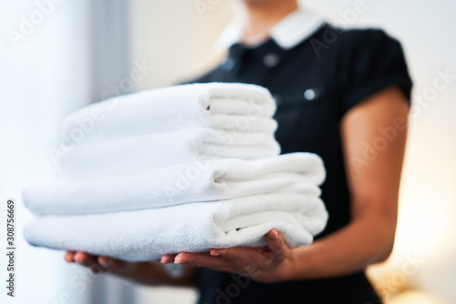 Maid with fresh towels in hotel room Fototapeta