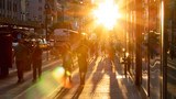 Fototapeta Nowy Jork - Sunlight shines on the diverse crowds of people walking down the busy sidewalk on 34th Street through Midtown Manhattan in New York City