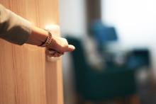 Half-open Door Of A Hotel Bedroom With Hand