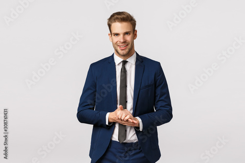Handsome and confident, smart male entrepreneur in classic suit, rubbing palms a Wallpaper Mural