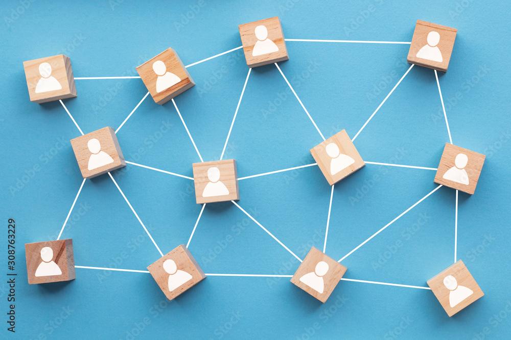 Fototapeta Wooden blocks connected together on a blue background. Teamwork concept
