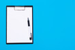 Clipboard with white sheet and pen on a blue background. View from above. space for text