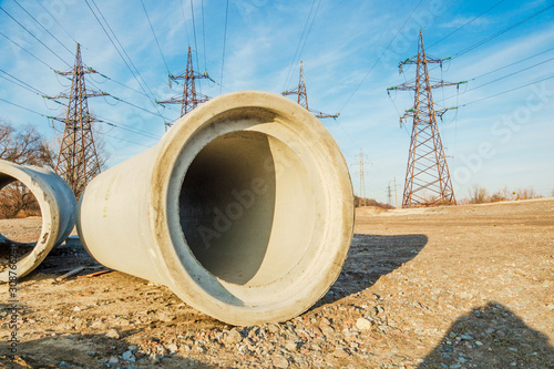 Fototapeta Large concrete pipe for the construction of sewers on the background of high voltage poles obraz