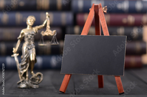 Fototapeta Lady Justice and mini Blackboard on wooden background in front of law books libr