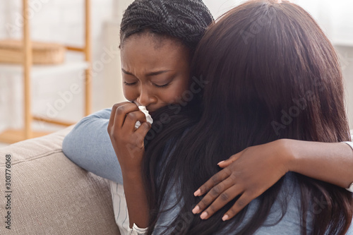 Fotografiet Woman hugging her crying girlfriend, supporting her after receiving bad news