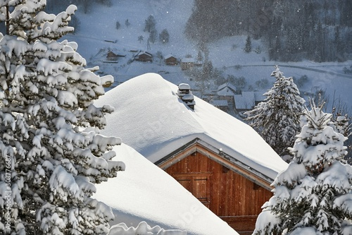 fototapeta na lodówkę House roof covered with falling snow in a beautiful mountain scenery, idyllic winter atmosphere