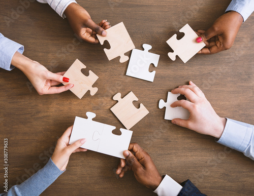 Group of business people assembling jigsaw puzzle together Canvas Print