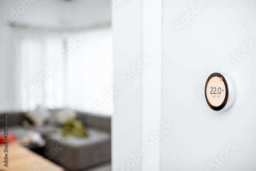 Fotomural Round smart thermostat with touch screen installed on the wall indoors
