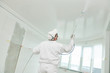 Leinwanddruck Bild - Painter worker with airless painting sprayer covering ceiling surface into white
