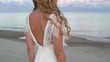 Back of a beautiful bride in a wedding dress walking on the seashore on background of the rose sunset cloud