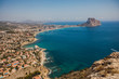 Beautiful super wide-angle aerial view of Calpe, Calp, Spain with harbor and skyline, Penon de Ifach mountain, beach and scenery beyond the city, seen from Mirador Monte Toix mountain viewpoint