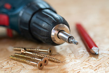 Electric Screwdriver, Self Drilling Screws And Carpenter Pencil Lying On Chip Board. Blurred Background.