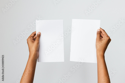 Obraz Studio shot of an ethnic or black model holding an A5 or folded letter size blank mockup - fototapety do salonu
