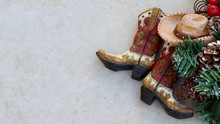 Brown And Tan Rustic Cowboy Boots And Hat With Christmas Decorations Laying  On A Tan Background With Copy Space