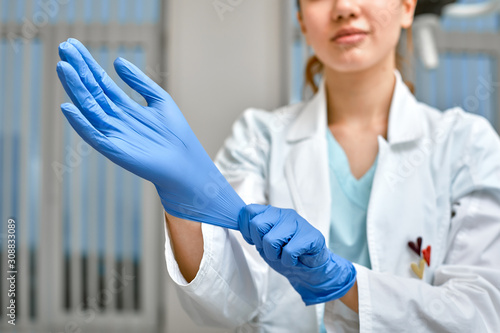 Obraz na plátně Close up of a female doctor putting a blue latex gloves on a clinic background