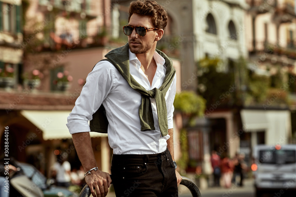 Fototapeta Stylish man wearing sunglasses and white shirt with tied sweater on shoulders