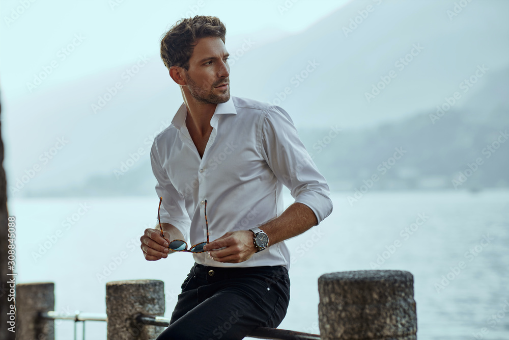 Fototapeta Stylish man in white classic shirt, looking at the mountains view